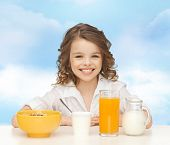 healthy food, eating, people and children concept - happy smiling beautiful girl having breakfast over blue sky background