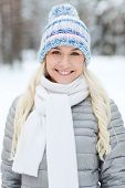 season, christmas and people concept - happy smiling young woman in winter forest