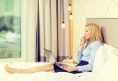 business, technology, internet and hotel concept - happy businesswoman with phone and laptop lying in hotel in bed