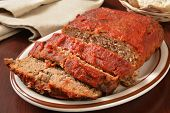 image of meatloaf  - A serving platter with sliced meatloaf covered in tomato sauce - JPG