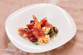 Shrimps with bacon, olives and rosemary in plate on table