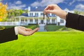 stock photo of key  - Real Estate Agent Handing Over the House Keys in Front of a Beautiful New Home - JPG
