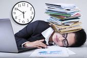 stock photo of indian  - Portrait of indian entrepreneur sleeping in the office with paperwork over her head - JPG