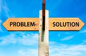stock photo of arrow  - Wooden signpost with two opposite arrows over clear blue sky Problem versus Solution messages Problems solving conceptual image - JPG