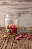 Glass Jar With Color Chocolate On A Wooden Board
