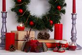 Christmas decoration with wreath, candles and present boxes on shelf on white wall background