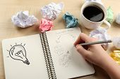 Female hand writing at notebook with cup of coffee at wooden desk background