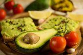 stock photo of avocado  - halved avocado and avocado sandwich on a cutting board - JPG