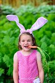 Young Girl Wearing Bunny Ears With Carrot In Her Mouth