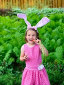 Little Girl Wearing Bunny Ears Eating A Carrot
