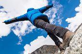 Female Catching Balance On Mountain Ridge