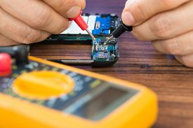 image of ohm  - Close-up Of Human Hand Repairing Cellphone With Multimeter ** Note: Shallow depth of field - JPG