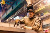 stock photo of protective eyewear  - Young man with protective mask welding in a factory - JPG