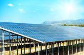 stock photo of environmentally friendly  - Many solar panels that produce green environmentally friendly energy with bright sun on the blue sky - JPG