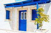 image of windows doors  - Iconic view on wooden blue doors and windows with shade from roofing typical for Greece - JPG
