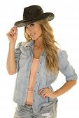stock photo of cowgirls  - A cowgirl touching the brim of her western hat - JPG