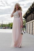 stock photo of evening gown  - Barefoot blond woman wearing evening peach color gown standing on a deck with lake behind her and holding silver sandals - JPG