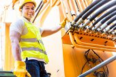stock photo of motor vehicles  - Asian motor mechanic standing in front of construction or mining machinery in vehicle workshop - JPG