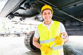 picture of motor vehicles  - Asian motor mechanic working on construction or mining machinery in vehicle workshop - JPG