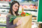 picture of supermarket  - Smiling woman shopping in a supermarket - JPG