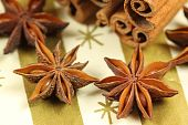 stock photo of ouzo  - Anise stars and cinnamon on golden background - JPG