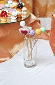 picture of lollipop  - Colorful lollipops on white table. Heart and round shaped lollipops placed in a glass on table