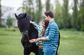 stock photo of appaloosa  - pair of lovers walk with a horse  - JPG