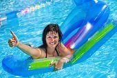 foto of mattress  - Woman  swimming on inflatable beach mattress thumb up - JPG