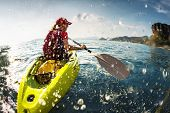 picture of kayak  - Young lady paddling the kayak in the sea with lots of splashes - JPG