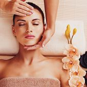 foto of low-necked  - Masseur doing massage the head of an adult woman in the spa salon - JPG