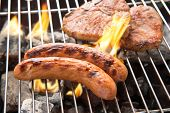 picture of grilled sausage  - Grilled sausage and pork chop on the flaming grill - JPG