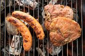stock photo of grilled sausage  - Grilled sausage and pork chop on the flaming grill - JPG