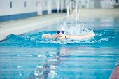 pic of goggles  - Young woman in goggles and cap swimming butterfly stroke style in the blue water indoor race pool - JPG
