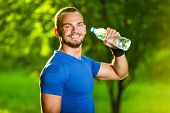 stock photo of cold-shoulder  - Athletic sport man drinking water from a bottle - JPG