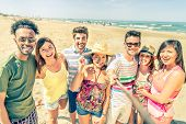 image of stick  - Multi ethnic group of friends enjoying vacation and taking a picture with selfie stick - Mixed group of several people having fun on the beach ** Note: Shallow depth of field - JPG