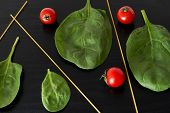 foto of black-cherry  - Still life with cherry tomatoes and spinach on black background - JPG