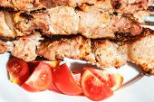 picture of kebab  - pieces of pieces of red tomato and shish kebabs on skewers on plate close up - JPG