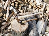 stock photo of cleaving  - pile of wood deck for chopping firewood two axes on village yard - JPG