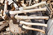 foto of cleaving  - many various axes in wood block near stack of firewoods - JPG