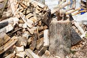 image of cleaving  - pile of firewoods and several axes in wooden block in village - JPG