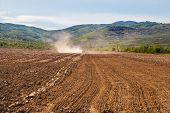 picture of plowing  - A tractor is cultivating the soil before sowing in the early spring - JPG