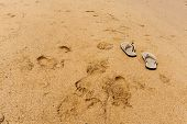 stock photo of footprints sand  - footprints and slipper on sand beach Pattaya Thailand - JPG