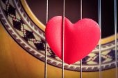 picture of heart sounds  - A red love heart in the strings of a guitar - JPG