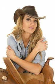 pic of western saddle  - a cowgirl with her western hat on leaning on her saddle - JPG