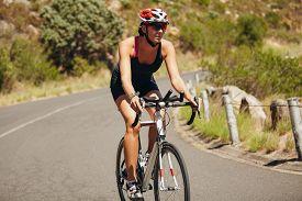 foto of triathlon  - Young woman triathlon athlete cycling - JPG