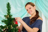 stock photo of tawdry  - Young pregnant girl dresses up Christmas tree - JPG