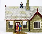 pic of eviction  - A couple who have just been evicted from there house carrying suitcases with the bank manager sat comfortably on the top of their house gloating at the thought of selling the house and making money - JPG