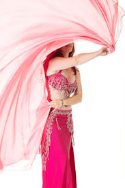 stock photo of belly-dance  - Lithe adult caucasian belly dancer with red hair and pink belly dancing outfit performing a dance with veils on a white background - JPG