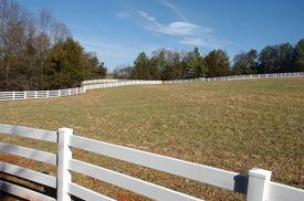 stock photo of white vinyl fence  - White Horse Fence On Sprawling Horse Ranch - JPG
