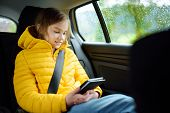 Adorable Girl Sitting In A Car And Reading Her Ebook On Rainy Autumn Day. Child Entertaining Herserf poster